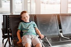 Tired child sleeping in waiting room for passengers. Stock Photos