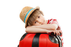 The tired child with suitcase. The tired child with red trunk stock photography
