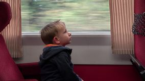 Tired child in the train looking on the window and singing. UHD 4K stock video