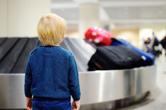 Tired child waiting baggage at the airport. Cute little tired kid boy at the airport, traveling. Upset child waiting with kids suitcase on baggage carousel Royalty Free Stock Image