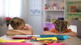 Tired children falling asleep sitting at desk, exhausting after-school education. Stock photo royalty free stock images