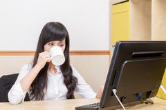 Tired Chinese Businesswoman drinking coffee stock photo