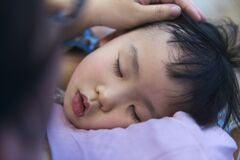 Tired Chinese kid sleeping on mom`s shoulder closeup portrait
