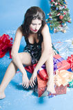 Tired Christmas girl. A studio view of a teenage girl in a party dress, sitting on a pile of presents, looking tired and worn out from Christmas preparation and Royalty Free Stock Images