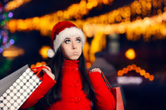 Tired Christmas Woman With Shopping Bags. Funny girl in red coat looking for presents in Xmas fair Royalty Free Stock Image