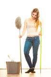 Tired cleaning woman mopping floor. Cleanup housework concept. Tired cleaning lady young woman mopping floor, holding two mops new and old white background Royalty Free Stock Image