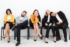 Tired colleagues sitting in office while sleeping. Stock Photos