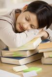 Tired college student sleeping on pile of books Royalty Free Stock Image