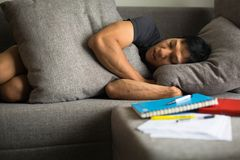 A tired college student taking a nap after studying stock photo