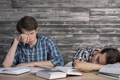 Tired college students. Two young college students tired of studying at wooden table with many open books. Textured wooden wall in the background Royalty Free Stock Images