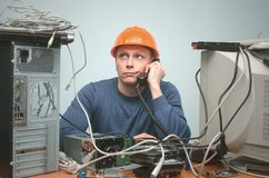 Computer technician specialist. PC repairman. Tired computer technician is consulting a users by their questions by the phone. PC repair service center Royalty Free Stock Image