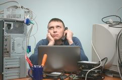 Computer technician specialist. PC repairman. Tired computer technician is consulting a users by their questions by the phone. PC repair service center Royalty Free Stock Photos