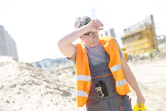 Tired construction worker wiping forehead at site Stock Images