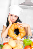 Tired cook. Tired and bored cook with bread and vegetables in the kitchen at home Royalty Free Stock Photos