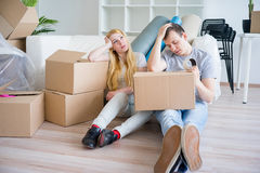 Tired couple with boxes. Moving into new home royalty free stock images