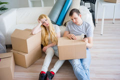 Tired couple with boxes. Moving into new home royalty free stock image