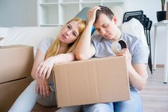 Tired couple with boxes. Moving into new home stock photography