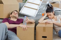 Tired couple with boxes moving into new home apartment. Boxes royalty free stock image