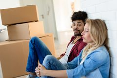 Tired couple with boxes moving into new home. Apartment stock photos