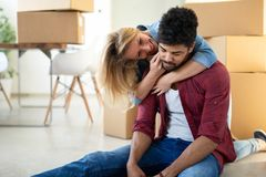 Tired couple with boxes moving into new home. Apartment stock photography
