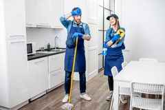 Tired couple of cleaners in the kitchen. Portrait of a tired couple standing as a professional cleaners in uniform during the break in the kitchen royalty free stock photography