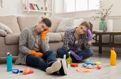 Tired couple with cleaning equipment at home. Tired couple after cleaning their home. Young men and girl sitting on floor with sponges, brushes and detergents at stock photo