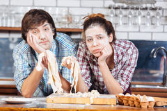 Tired couple with flour on faces kneading dough at kitchen Royalty Free Stock Photography