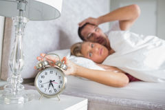 Tired couple looking at alarm clock in the morning with woman tu Stock Photos
