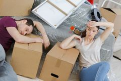 Tired couple resting in new home during moving royalty free stock photography