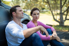 Tired couple sitting by breakdown car Stock Photos