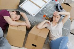Tired couple sitting on floor at new home. Couple stock photos