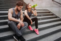 Tired couple is sitting together close to each other after running. He is looking down and keeping his hands crossed. While she is drinking water from the royalty free stock photo