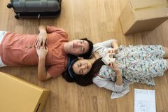 Tired couple sleep on room with moving box. Top view or flat lay portrait of tired Asian couple sleeping on wooden floor with many moving cardboard boxes Royalty Free Stock Photo