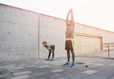 Tired couple stretching after exercise. Fitness, sport, exercising, training and people concept - tired couple stretching after exercise outdoors on city street Stock Photography