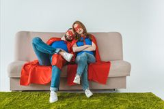 Tired couple in superhero costumes sleeping while sitting on sofa. On grey stock photos