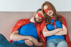 Tired couple of superheroes in masks and cloaks sleeping together. On couch stock photo