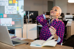 Tired creative businesswoman sitting on desk Royalty Free Stock Image