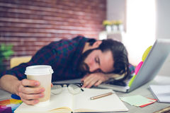 Tired creative editor holding disposable cup. While sleeping on office desk royalty free stock image