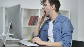 Tired Creative Man Yawning at Work in Front of Desktop. The Tired Creative Man Yawning at Work in Front of Desktop, high quality stock video footage