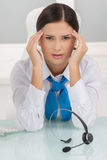 Tired customer service representative. Depressed young female customer service representative sitting at her working place and holding her head in hands Royalty Free Stock Images