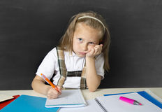 Tired cute junior schoolgirl with blond hair sitting in stress working doing homework looking bored. Sad and tired cute junior schoolgirl with blond hair sitting Royalty Free Stock Photography