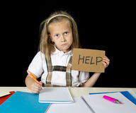 Tired cute junior schoolgirl with blond hair sitting in stress working doing homework looking bored Stock Images