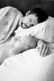Tired dad and baby son sleeping Stock Photography