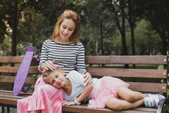 Tired cute daughter lying on her mother knees royalty free stock photo