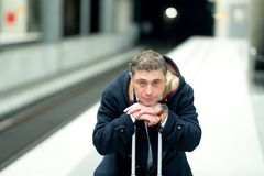 Crouched man waiting for the train. Tired and demoralised traveler waiting for his delayed train Stock Photography