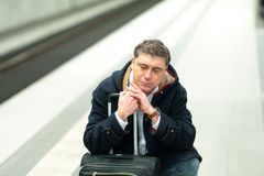 Crouched man waiting for the train. Tired and demoralised traveler waiting for his delayed train Royalty Free Stock Photo