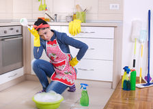 Tired and depressed cleaning lady in kitchen stock images