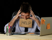 Tired desperate businessman in stress working at office computer desk holding sign asking for help Royalty Free Stock Photos