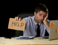 Tired desperate businessman in stress working at office computer desk holding sign asking for help. Young desperate businessman suffering stress working at Royalty Free Stock Image