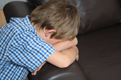 Tired or distressed little boy, face down on sofa royalty free stock photos